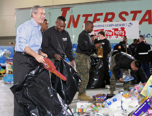 "President George W. Bush helps U.S. Marines sort through a stack of toys Monday, Dec. 19, 2005 at the ""Toys for Tots"" collection center at the Naval District Washington Anacostia Annex in Washington, D.C. White House photo by Kimberlee Hewitt"