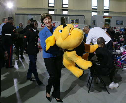 "Mrs. Laura Bush helps carry a large stuffed animal to a toy distribution vehicle, Monday, Dec. 19, 2005, at the ""Toys for Tots"" collection center at the Naval District Washington Anacostia Annex in Washington, D.C., where she joined President George W. Bush in thanking the U.S. Marines for their charitable efforts. White House photo by Shealah Craighead"
