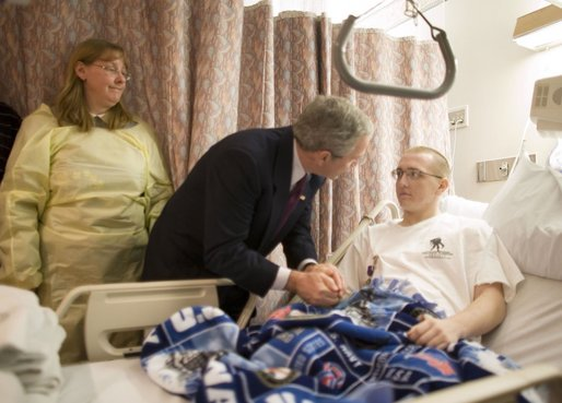 President George W. Bush grasps the hand of U.S. Navy Hospitalman Apprentice Tony Bullene of Watertown, S.D., after presenting him with a Purple Heart, with his mother, Carol Bullene, looking on Wednesday, Dec. 21, 2005, at the National Naval Medical Center in Bethesda, Md. White House photo by Paul Morse
