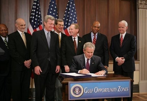 President George W. Bush signs H.R. 4440, the Gulf Opportunity Zone Act of 2005, Wednesday Dec. 21, 2005, as administration officials and legislative members join him for the signing ceremony held in the Dwight D. Eisenhower Executive Office Building in Washington. White House photo by Paul Morse