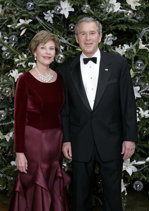 "President George W. Bush and Laura Bush stand before the White House Christmas tree in the Blue Room of the White House. In keeping with this year's theme, ""All Things Bright and Beautiful!"" the Fraser fir is decorated with fresh white lilies. White House photo by Eric Draper"