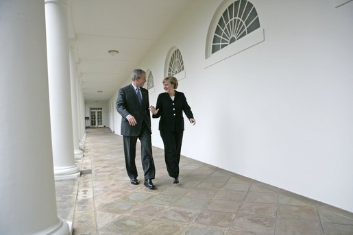 President George W. Bush and German Chancellor Angela Merkel walk along the colonnade in the Rose Garden during her first visit to the White House Friday, Jan. 13, 2006. White House photo by Eric Draper
