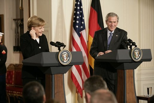 Chancellor Angela Merkel of Germany, adjusts her earpiece as President George W. Bush begins his remarks during a joint press availability Friday, Jan. 13, 2006, in the East Room of the White House. White House photo by Eric Draper