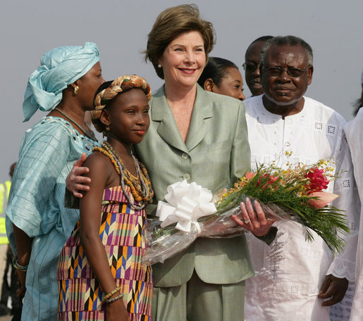 Mrs. Laura Bush stands with 10-year-old Aisha Garuba Sunday, Jan. 15, 2006, after she presented Mrs. Bush with flowers upon her arrival at Kotoka International Airport in Accra, Ghana. White House photo by Shealah Craighead