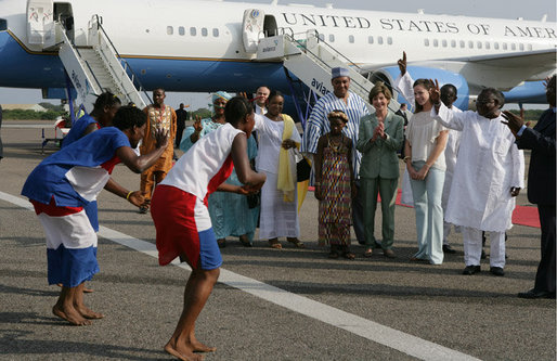Mrs. Laura Bush and her daughter Barbara Bush are greeted by a cultural dance troupe upon their arrival Sunday, Jan. 15, 2006 at Kotoka International Airport in Accra, Ghana. White House photo by Shealah Craighead