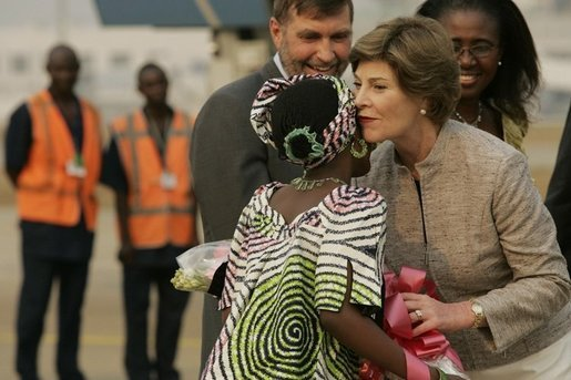 Mrs. Laura Bush embraces 11-year-old Jamila Ahmed after she presented flowers to Mrs. Bush, Tuesday, Jan. 17, 2006, upon her arrival to Abuja, Nigeria. Deputy Chief of U.S. Mission Thomas Fuery and Nigeria's Minister of Education Chinwe Obaji, are seen in the background. White House photo by Shealah Craighead