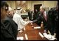 President George W. Bush exchanges handshakes with Mr. Mohammed Jaber during a visit at the White House Wednesday, Jan. 18, 2006, with victims of Saddam Hussein. Mr. Jaber is a former Iraqi journalist who was jailed for writing a story that raised questions about how oil money was being spent. White House photo by Eric Draper
