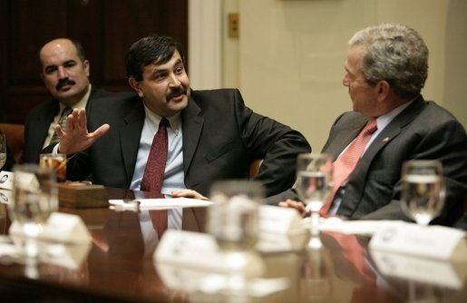 President George W. Bush listens to Mr. Raid Mohammad Wednesday, Jan. 18, 2006, during a visit at the White House with victims of Saddam Hussein. Mr. Mohammad's father was a journalist in Iraq who imprisoned and eventually killed by Saddam's men. White House photo by Eric Draper