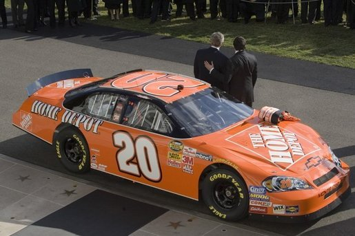 President George W. Bush stands with champion race car driver Tony Stewart, during ceremonies to honor the 2005 NASCAR Nextel Cup Champion team, Tuesday, Jan. 24, 2006, on the South Lawn of the White House. White House photo by Eric Draper