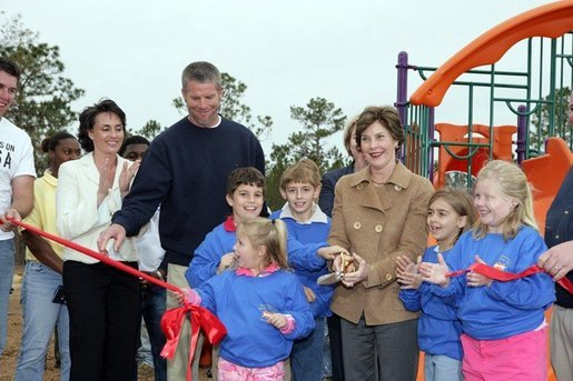 Laura Bush attends a ribbon cutting ceremony with football star Brett Favre and his wife, Deanna, left, at the Kaboom Playground, built at the Hancock North Central Elementary School in Kiln, Ms., Wednesday, Jan. 26, 2006, during a visit to the area ravaged by Hurricane Katrina. White House photo by Shealah Craighead
