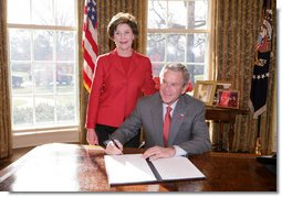President George W. Bush is joined by Laura Bush, Wed. Feb. 1, 2006 in the Oval Office at the White House, as he signs a proclamation in honor of American Heart Month.  White House photo by Paul Morse