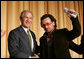 "President George W. Bush shakes hands with Bono after the musician spoke Thursday morning, Feb. 2, 2006, during the National Prayer Breakfast. President Bush called the rock star a ""doer"" and a ""good citizen of the world."" White House photo by Paul Morse"