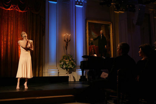 President George W. Bush and Laura Bush listen to country music artist LeAnn Rimes perform in the East Room of the White House during a dinner honoring The Dance Theatre of Harlem Monday, February 6, 2006. White House photo by Shealah Craighead