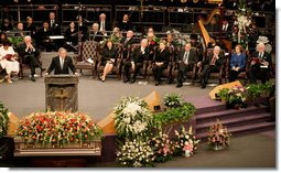 President George W. Bush addresses guests at the homegoing celebration for Coretta Scott King, Tuesday, Feb. 7, 2006 at the New Birth Missionary Church in Atlanta, Ga. In the background-right are Mrs. Laura Bush, former President Bill Clinton, U.S. Sen. Hillary Clinton, former President George H. W. Bush, former President Jimmy Carter, Mrs. Roslyn Carter and U.S. Sen. Edward M. Kennedy.  White House photo by Eric Draper