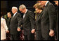 President George W. Bush and Mrs. Laura Bush are seen during a prayer holding hands with former President Bill Clinton, right, and Rev. Robert Schuller, left, at the homegoing celebration for Coretta Scott King, Tuesday, Feb. 7, 2006 at the New Birth Missionary Church in Atlanta, Ga. White House photo by Eric Draper