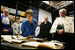 Laura Bush looks at books dating to the 1500's during a tour of the Ancient Library at the University of Turin guided by Paolo Novaria, Archives, left, and Enrico Artifoni, right, Saturday, Feb. 11, 2006, in Turin, Italy. White House photo by Shealah Craighead