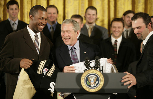 President George W. Bush is presented with a Chicago White Sox jacket and baseball jersey, Monday, Feb. 13, 2006 by White Sox players Jermaine Dye, left, and Paul Konerko in the East Room of the White House, where President Bush honored the 2005 World Series Champions. White House photo by Eric Draper