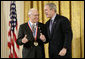 President George W. Bush presents a National Medal of Science, Monday, Feb. 13, 2006 to Dr.Norman E. Borlaug of Texas A&M University, during ceremonies in the East Room of the White House. Borlaug was honored for his work in creating disease resistant and high-yield wheat, providing a new quality food source for millions of people around the world. White House photo by Eric Draper