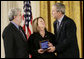 President George W. Bush presents a National Medal of Technology, Monday, Feb. 13, 2006 to George Lucas, left, and Chrissie England, of Industrial Light and Magic of San Francisco, Calif., during ceremonies in the East Room of the White House. White House photo by Eric Draper