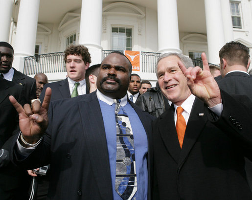President George W. Bush poses with University of Texas Longhorns assistant coach Jeff 'Mad Dog' Madden, as they give the 'Hook Em Horns' sign, Tuesday, Feb. 14, 2006 on the South Lawn of the White House, during ceremonies to honor the 2005 NCAA Football Champions. White House photo by Paul Morse