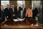 President George W. Bush is joined by legislators and the chairman of the Federal Deposit Insurance Corporation, Wednesday, Feb. 15, 2006 in the Oval Office, as he signs H.R. 4636- The Federal Deposit Insurance Reform Conforming Amendments Act of 2005. From left to right are U.S. Rep. Spencer Bachus, R-Ala., U.S. Sen. Tim Johnson, D-S.D., U.S. Sen Paul Sarbanes, D-Md., U.S. Sen. Richard Shelby, R-Ala., U.S. Rep. Mike Oxley, R-Ohio, U.S. Rep. Darlene Hooley, D-Ore., U.S. Sen. Mike Enzi, R-Wyo., and Martin Gruenberg, acting chairman of the Federal Deposit Insurance Corporation. White House photo by Kimberlee Hewitt