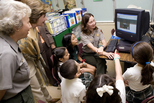 Laura Bush and Fran Mainella look on as students of Stella Summer's Gifted Science class work with Ranger Maria Beotegui Thursday, Feb. 16, 2006, to navigate through Web Rangers, the online version of Junior Rangers, during a visit to Banyan Elementary School in Miami, FL. The National Junior Ranger Programs promote knowledge of science, history, the environment and learning through fun. White House photo by Shealah Craighead