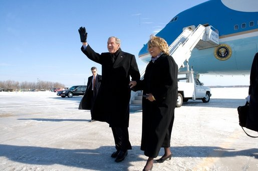 President George W. Bush escorts Freedom Corps Greeter Beverly Christy-Wright after his arrival in Milwaukee, Wisconsin, Monday, Feb. 20, 2006. The President presented Beverly with the President's Volunteer Service Award. White House photo by Eric Draper