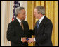 President George W. Bush congratulates Dr. Carl Anderson of Washington, upon receiving the President's Volunteer Service Award during a White House celebration of African American History Month. White House photo by Paul Morse