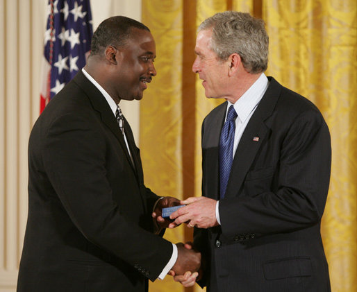 President George W. Bush congratulates Steve Ellis of Carrollton, Texas, upon receiving the President's Volunteer Service Award during a White House celebration of African American History Month. White House photo by Paul Morse