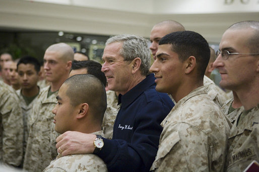 President George W. Bush poses for photos with U.S. Marines headed to Iraq, during a stopover Tuesday evening, Feb. 28, 2006 at Shannon, Ireland's international airport terminal. President George W. Bush meets with U.S. Marines headed to Iraq, during a stopover Tuesday evening, Feb. 28, 2006 at Shannon, Ireland's international airport terminal. President Bush visited with the Marines as part of his five-day visit to India and Pakistan. White House photo by Paul Morse