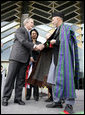 President George W. Bush and Afghanistan President Hamid Karzai shake hands after cutting the ceremonial ribbon, Wednesday, March 1, 2006, to dedicate the new U.S. Embassy Building in Kabul, Afghanistan. President Karzai thanked President Bush and the American people for their continued support to the Afghan people. White House photo by Eric Draper