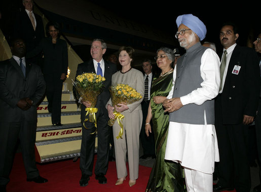 President George W. Bush and Mrs. Bush stand with flowers presented upon their arrival Wednesday, March 1, 2006, at New Delhi's Indira Gandhi International Airport where they were greeted by India's Prime Minister Manmohan Singh, right, and his wife, Gursharan Kaur. White House photo by Eric Draper