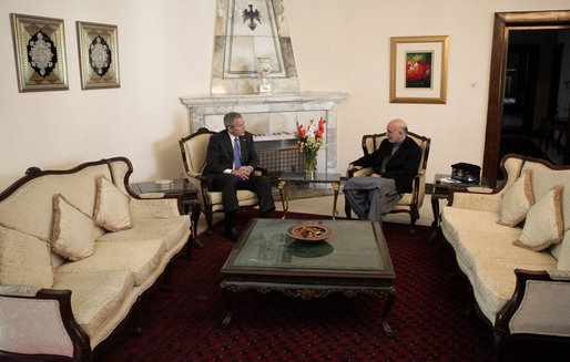 President George W. Bush and Afghan President Hamid Karzai talk Wednesday, March 1, 2006, in the Presidential Palace in Kabul. President and Mrs. Bush made the surprise five-hour stop in Afghanistan en route to India. White House photo by Eric Draper