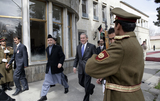 President George W. Bush is accompanied by Afghan President Hamid Karzai at the Presidential Palace in Kabul after President and Mrs. Bush landed in Afghanistan for a brief visit en route to India. During their five-hour stop, they participated in a ceremonial ribbon-cutting at the U.S. Embassy and visited with troops at Bagram Air Base north of the city. White House photo by Eric Draper