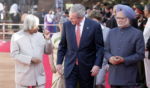 President George W. Bush listens to India's President A.P.J. Abdul Kalam as they walk the red carpet with Prime Minister Manmohan Singh during the arrival ceremony in New Delhi Thursday, March 2, 2006, welcoming the President and Mrs. Bush to India. White House photo by Eric Draper