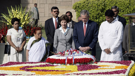 President George W. Bush and Laura Bush are joined by Rajnish Kumar, right, Secretary of the Rajghat Samadhi Committee, and Dr. Nirmila Deshpande, co-Chair of the Rajghat Gandhi Samadhi committee, for a moment of silence at the Mahatma Gandhi Memorial in Rajghat, India. White House photo by Eric Draper