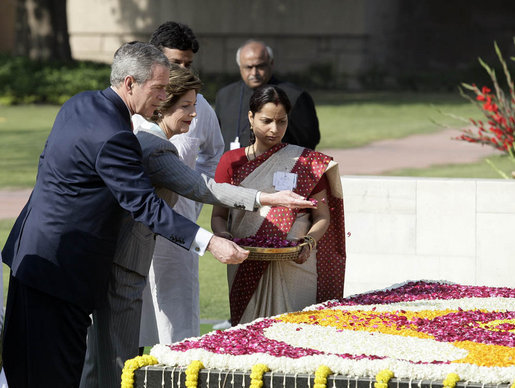President George W. Bush and Laura Bush sprinkle flowers on the south side of the Mahatma Gandhi Memorial Thursday, March 2, 2006, during a wreath-laying ceremony in Rajghat, India. White House photo by Eric Draper