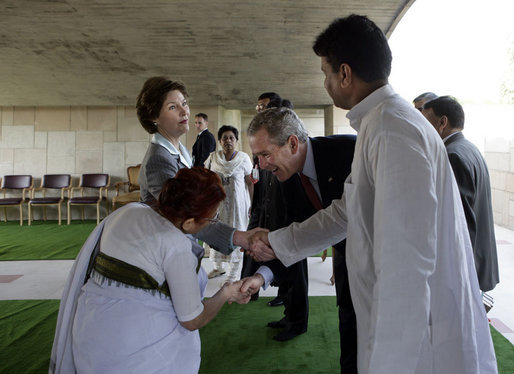 President George W. Bush reaches to shake the hand of Dr. Nirmila Deshpande, as Laura Bush exchanges handshakes with Rajnish Kumar after they were met by the pair Thursday, March 2, 2006 in Rajghat, India for the wreath-laying ceremony at the Mahatma Gandhi Memorial. White House photo by Eric Draper