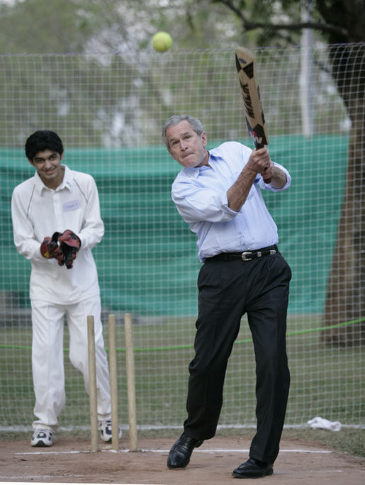 President George W. Bush watches his hit during a cricket clinic with Pakistani youth from the Schola Nova school and the Islamabad College for Boys, Saturday, March 4, 2006, at the Raphel Memorial Gardens on the grounds of the U.S. Embassy in Islamabad, Pakistan. White House photo by Eric Draper
