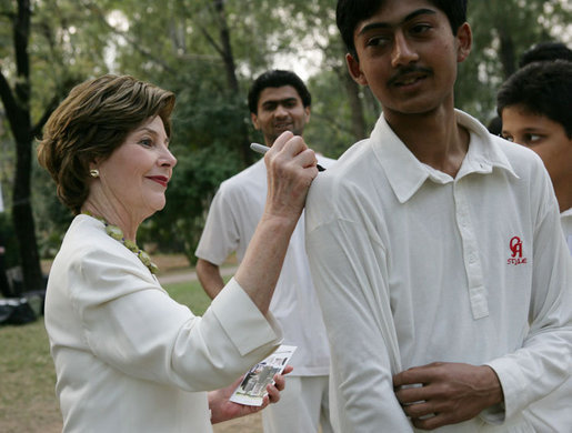 Mrs. Laura Bush signs the jerseys of students from the Schola Nova school and the Islamabad College for Boys, Saturday, March 4, 2006, who participated in a cricket clinic with President George W. Bush at the Raphel Memorial Gardens on the grounds of the U.S. Embassy in Islamabad, Pakistan. White House photo by Shealah Craighead