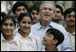 President George W. Bush poses with Pakistani youth from the Schola Nova school and the Islamabad College for Boys, Saturday, March 4, 2006, at the Raphel Memorial Gardens on the grounds of the U.S. Embassy in Islamabad, Pakistan, following his participation in a cricket clinic. White House photo by Eric Draper