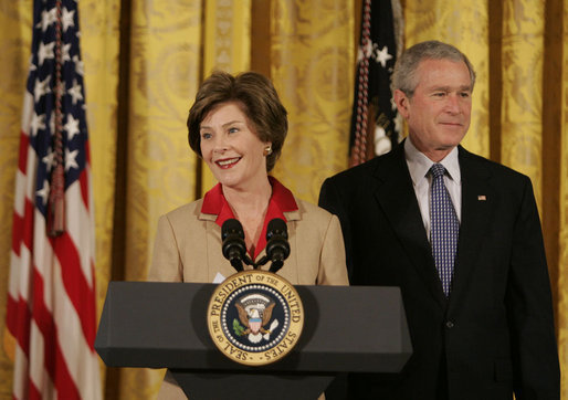 "President George W. Bush listens on as Mrs. Laura Bush welcomes women leaders to the East Room for a celebration Tuesday, March 7, 2006, of International Women's Day. Mrs. Bush said, ""I've been privileged to meet thousands of women from many nations, and I believe that women everywhere share the same dreams -- to be educated, to live in peace, to enjoy good health, to be prosperous, and to be heard."" White House photo by Kimberlee Hewitt"