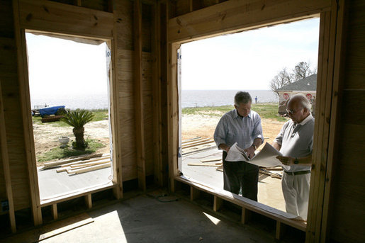 President George W. Bush looks over building plans with homeowner Jerry Akins at his home Wednesday, March 8, 2006 in Gautier, Miss., on the site where the Akins family is rebuilding their home destroyed by Hurricane Katrina. White House photo by Eric Draper
