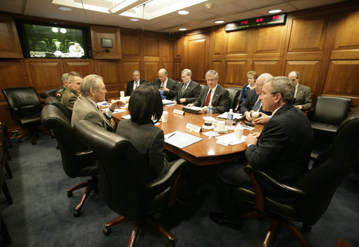 President George W. Bush meets with his National Security team in the White House Situation Room, Friday, March 10, 2006, on the latest developments in Iraq. At the table are Vice President Dick Cheney; Chief of Staff Andy Card; National Security Advisor Stephen Hadley; National Intelligence Director John Negroponte; Central Intelligence Agency Director Porter Goss; U.S. Army General John Abizaid; Chairman Joint Chiefs of Staff U.S. Marine General Peter Pace; Secretary of Defense Donald Rumsfeld and Secretary of State Condoleezza Rice. On screen are U.S. Ambassador to Iraq Zalmay Khalilzad, left, and U.S. Army General George Casey. Seated at far-right are White House Counsel Harriet Miers and Deputy National Security Advisor J. D. Crouch. White House photo by Eric Draper