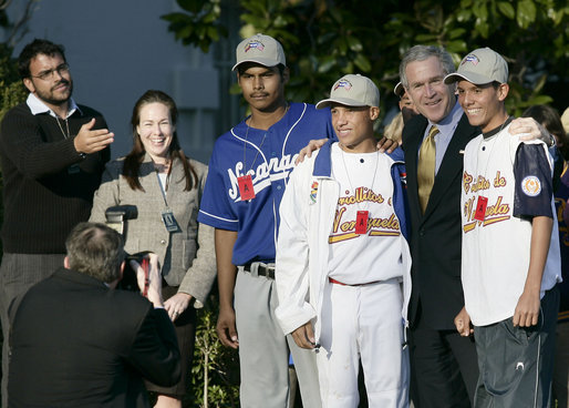 President George W. Bush poses for photographs with South American baseball players Tuesday, March 14, 2006, on the South Lawn of the White House. The players were guests at the arrival of Marine One after the President's trip to New York. The group is here on a State Department-funded International Sports Exchange centered around a shared passion of baseball and the inaugural World Baseball Classic. The players, from left, are: Geovanny Toval Monterrey, 17, from Nicaragua; Ronald Torreyes Solorzano, 14, from Venezuela; Bryan Guillen, 16, (in back) from Nicaragua, and Argerd Liendo Boada, 16, from Venezuela. White House photo by Eric Draper