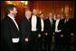 President George W. Bush is joined by House Speaker Dennis Hastert (R-Ill.), right, and Prime Minister Bertie Ahern of Ireland, as they stand with the McCrohan Tenors after the trio's performance Thursday, March 16, 2006, during a St. Patrick's Day Luncheon at the U.S. Capitol. White House photo by Kimberlee Hewitt