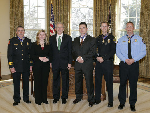 President George W. Bush meets Thursday, March 16, 2006 in the Oval Office of the White House with recipients of the Public Safety Officer Medals of Valor. From left to right are, Gene F. Large Jr., Fire Battalion Chief in Fort Walton Beach, Fla.; Marissa Hurst, wife of slain Officer Bryan S. Hurst of Columbus, Ohio; Peter Alfred Koe, Police Officer of Indianapolis, Ind.; Timothy Greene, Police Officer from Rock Hill, S.C.; and Firefighter Edward Frederic Henry of Charleston, S.C. White House photo by Paul Morse