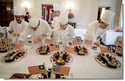 White House Executive Pastry Chef Thaddeus DuBois, center-background, supervises his staff, Tuesday, March 21, 2006, as they prepare the dessert trays for the social luncheon in honor of Liberia's President Ellen Johnson Sirleaf at the White House.  White House photo by Paul Morse