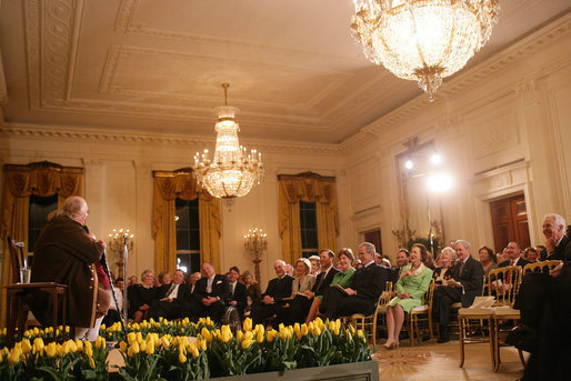 President George W. Bush and Mrs. Laura Bush join their invited guests in listening to Benjamin Franklin interpreter, Ralph Archbold of Philadelphia, Pa., Thursday evening, March 23, 2006 in the East Room of the White House, during a Social Dinner to honor the 300th birthday of Benjamin Franklin. White House photo by Shealah Craighead