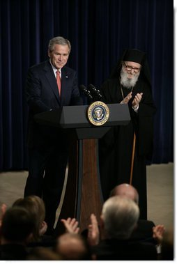 President George W. Bush is applauded by Archbishop Demetrios from the Greek Orthodox Church of America, Friday, March 24, 2006 at the Eisenhower Executive Office Building in Washington, where President Bush addressed an audience celebrating Greek Independence Day and honored the 185th anniversary of Greece's Independence.  White House photo by Eric Draper